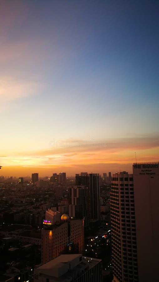 Sonnenuntergang in Unterlassungsgebäuden Bangkoks stockfoto
