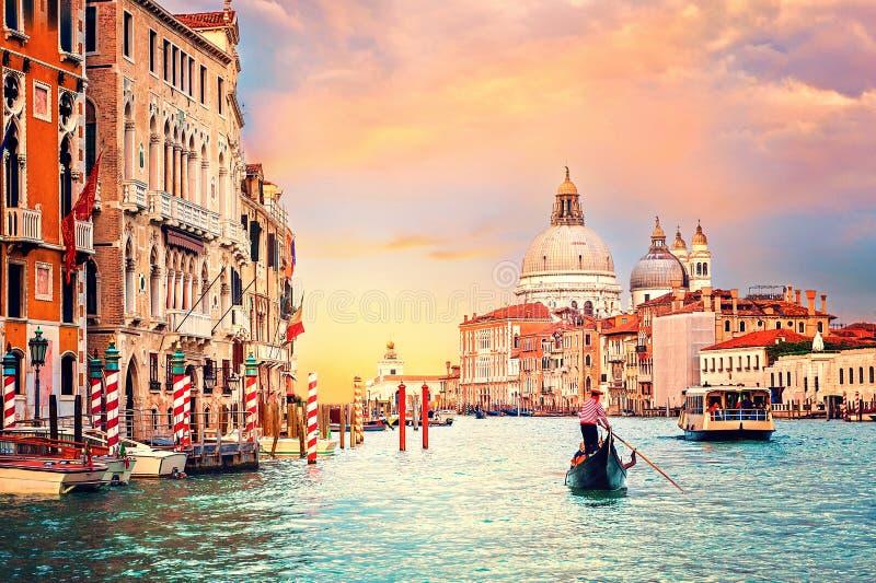 Sonnenuntergang in Venedig, Italien Boot und Gondel auf Grand Canal mit Basillica Santa Maria della Salute im Hintergrund stockfotografie