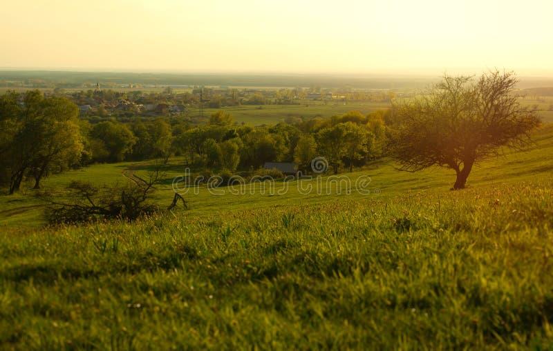 Sonnenuntergang-Wiese mit Weg zum entfernten Dorf lizenzfreie stockbilder