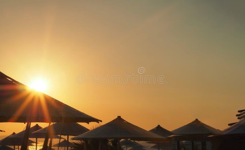 Sonnenuntergang zwischen Regenschirmen auf der Küste von Izmir-Ägäischem Meer lizenzfreies stockfoto