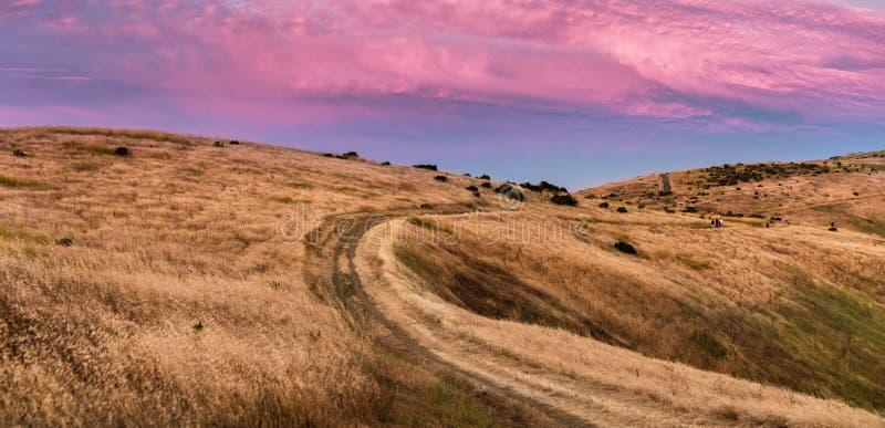 Sonnenuntergangansicht des Wanderwegs durch goldene Hügel in Santa Cruz-Bergen; Rosa und rote farbige Wolken, die den Himmel bede lizenzfreies stockfoto