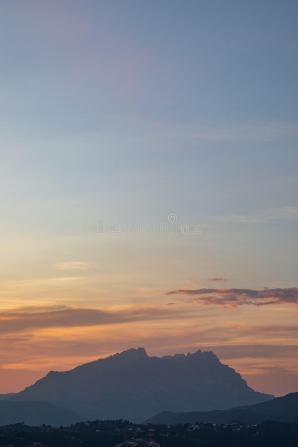 Sonnenuntergangansicht eines Gebirgszugs mit orange und blauem Himmel stockbilder