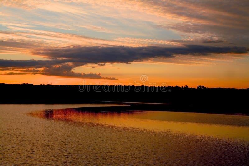 Sonnenuntergangfarben, die über den See nachdenken stockfoto