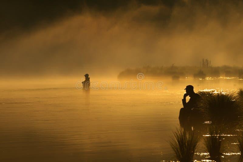 Sonnenuntergangfischen im Nebel lizenzfreie stockfotografie