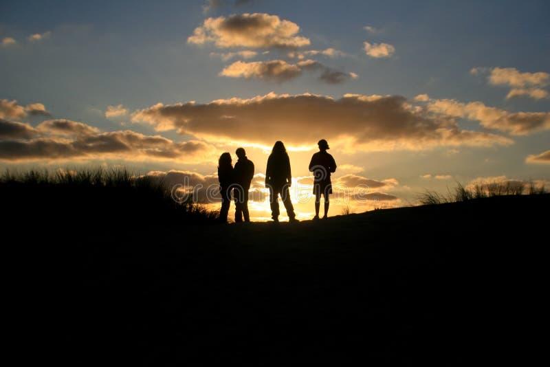 Sonnenunterganggruppenfreunde lizenzfreies stockfoto