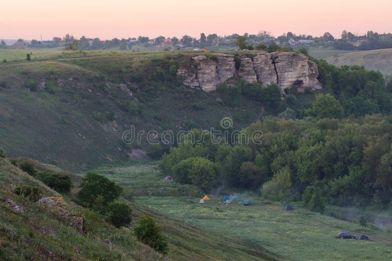 Sonnenunterganghimmel mit Felsen, Zelte, Vorgol-Fluss, Yelets, Russland lizenzfreies stockfoto