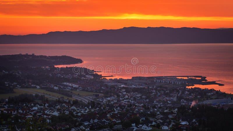 Sonnenunterganghimmel und entfernte Stadt Ranheim in Norwegen Entfernte Seeansicht stockbild