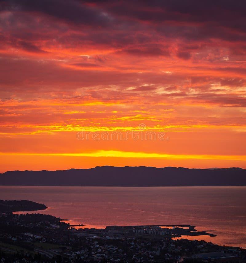 Sonnenunterganghimmel und entfernte Stadt Ranheim in Norwegen Entfernte Seeansicht lizenzfreies stockbild