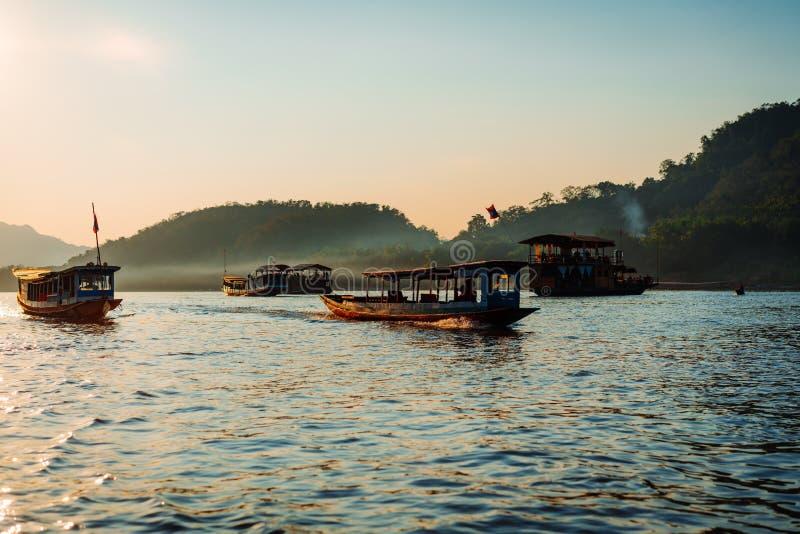 Sonnenuntergangkreuzfahrt in Luang Prabang auf dem Mekong Weiches Licht schlug die Boote im Wasser Die meisten ihnen sind auf ein stockfoto