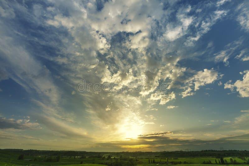 Sonnenunterganglandschaft mit Himmel und Wolken, Frühling des grünen Grases weit stockfotografie
