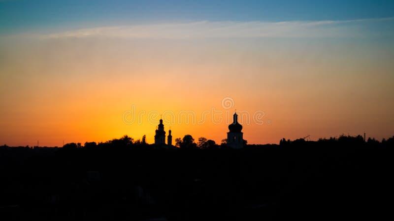 Sonnenunterganglandschaft mit orange Himmel und Schattenbildern von Kirchen stockfotos