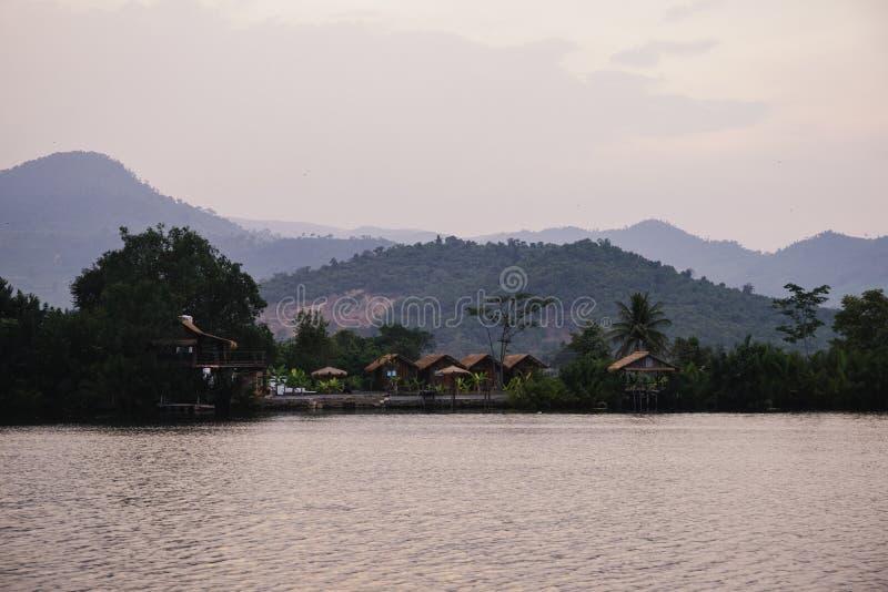 Sonnenunterganglandschaft mit rustikalem asiatischem Dorf Goldene Stundenansicht über kambodschanische Hütten im Berg Noch Fluss  lizenzfreies stockfoto