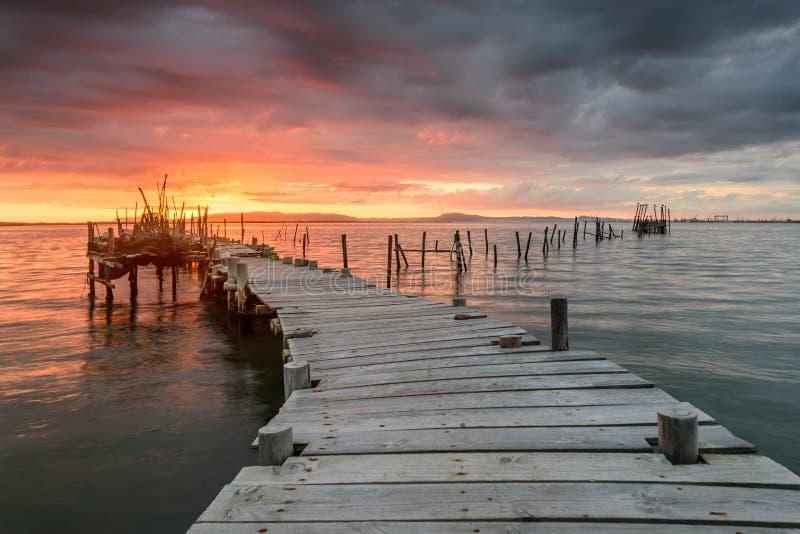 Sonnenunterganglandschaft von handwerklichen Fischerbooten im alten hölzernen Pier stockfotos
