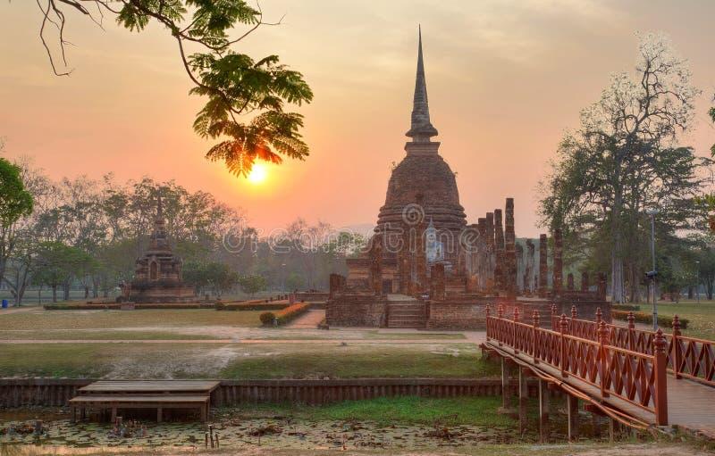 Sonnenunterganglandschaft von Wat Sa Si in historischem Park Sukhothai mit der untergehenden Sonne im Hintergrund, eine Holzbrück lizenzfreie stockfotografie