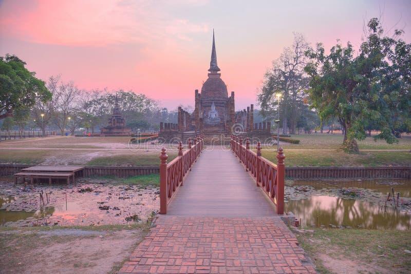 Sonnenunterganglandschaft von Wat Sa Si in historischem Park Sukhothai mit der untergehenden Sonne im Hintergrund, eine Holzbrück stockbilder