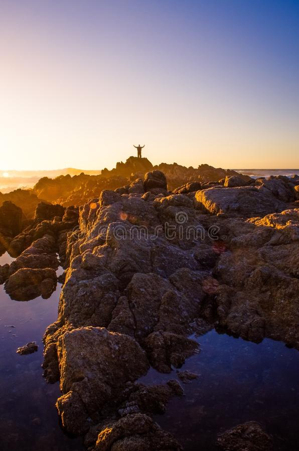 Sonnenuntergangmann-Meereswogefelsen stockbild