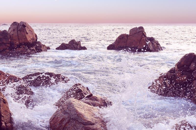 Sonnenuntergangmeerblick bei Sri Lanka Welle, die den Felsen zerschmettert Natürlicher Hintergrund im rosa Ton stockbilder