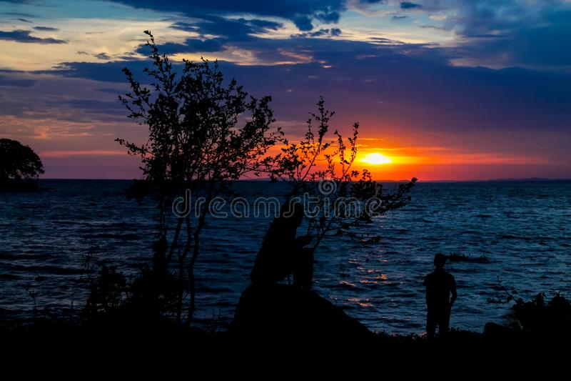 Sonnenuntergangschattenbild eines Mädchens und Junge am See stützen unter lizenzfreie stockbilder