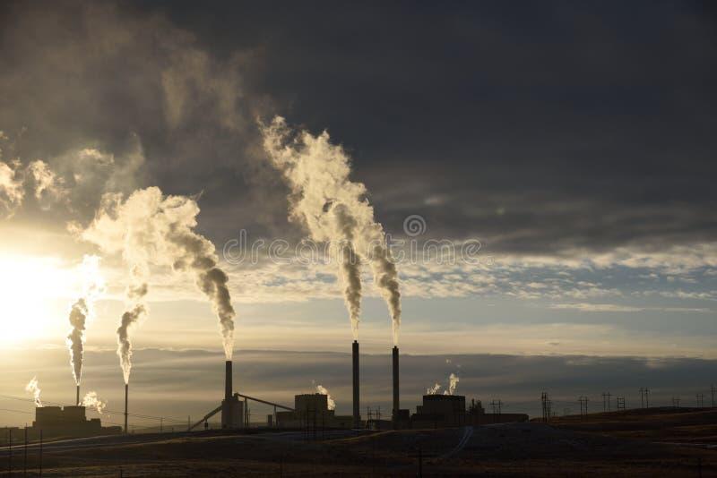 Sonnenuntergangschattenbild von den Schornsteinemissionen, die von einem kohlebeheizten Kraftwerk steigen stockfotos