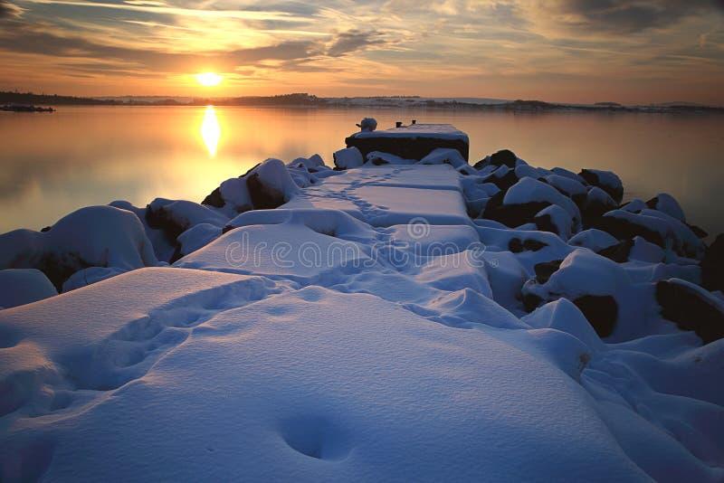 Sonnenuntergangsonne im Winter über dem schneebedeckten Pier stockbild