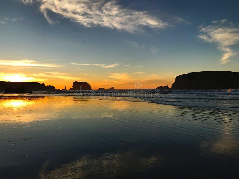 Sonnenuntergangstrand, -reflexionen und -wolken stockfoto