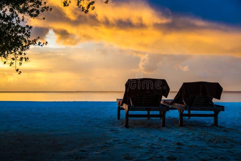 Sonnenuntergangstrandlandschaft mit sunbeds, Malediven stockfotos