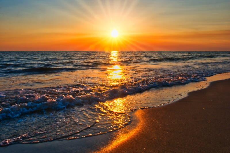 Sonnenuntergangstrandsonnenstrahlen stockbild