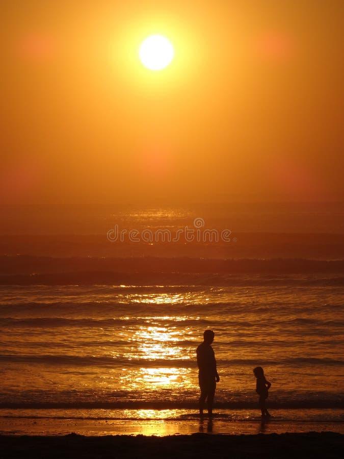 Sonnenuntergangstrandvater und -tochter lizenzfreie stockfotos