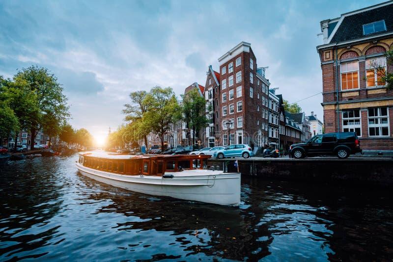 Sonnenuntergangszene in Amsterdam-Stadt Großes touristisches Boot auf dem berühmten niederländischen Kanal, der gekippte Häuser s stockbild