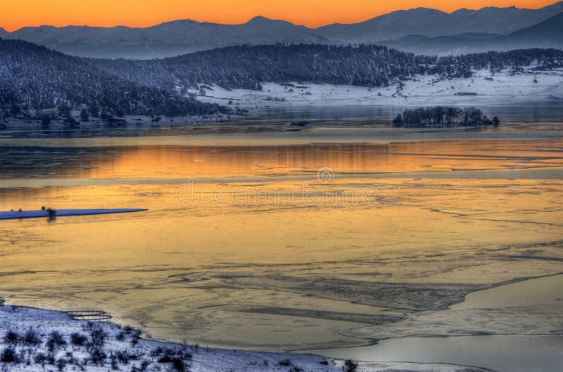 Sonnenuntergangwinterbild mit See lizenzfreie stockfotografie