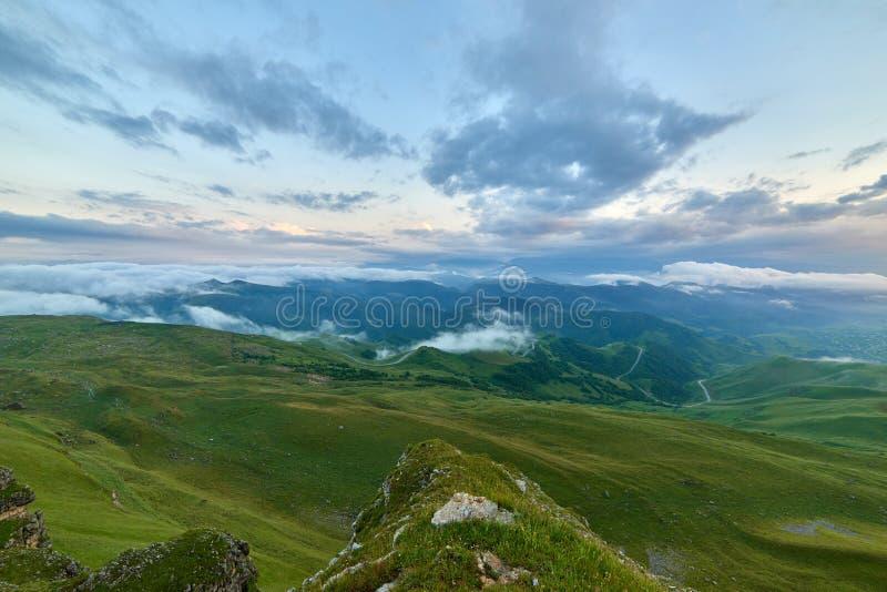 Sonnenuntergangwolken, blauer Himmel und Nebel über einem Gebirgsgrünen Tal mit einem Dorf und einer kurvenreichen Straße lizenzfreie stockfotos