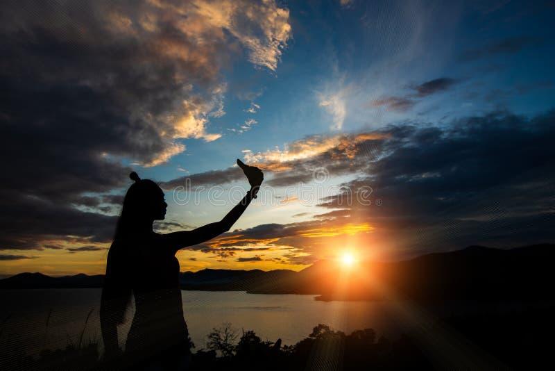 Sonnenuntergangwolkenstrahl zum jungen erwachsenen asiatischen woma stockfoto