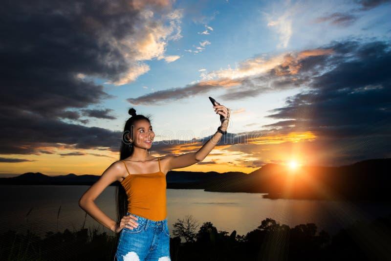 Sonnenuntergangwolkenstrahl zum jungen erwachsenen asiatischen woma lizenzfreies stockbild