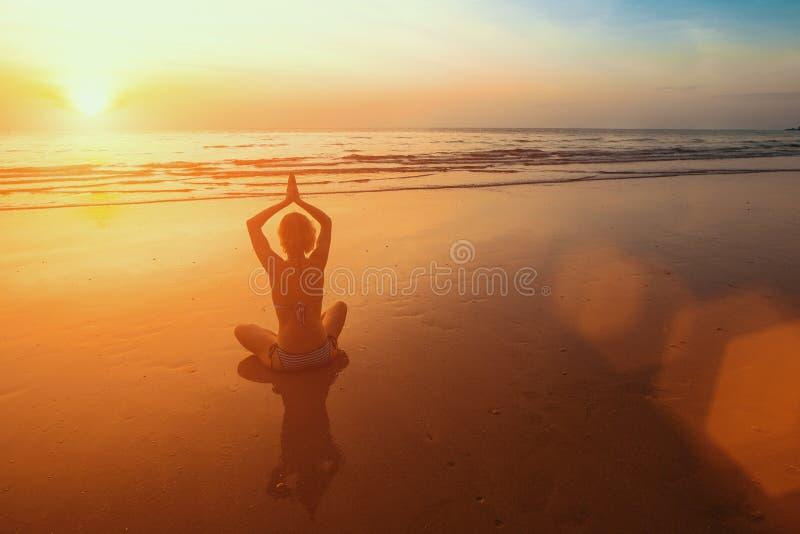 Sonnenuntergangyoga-Frauenmeditation auf Ozeanküste entspannen sich stockbild