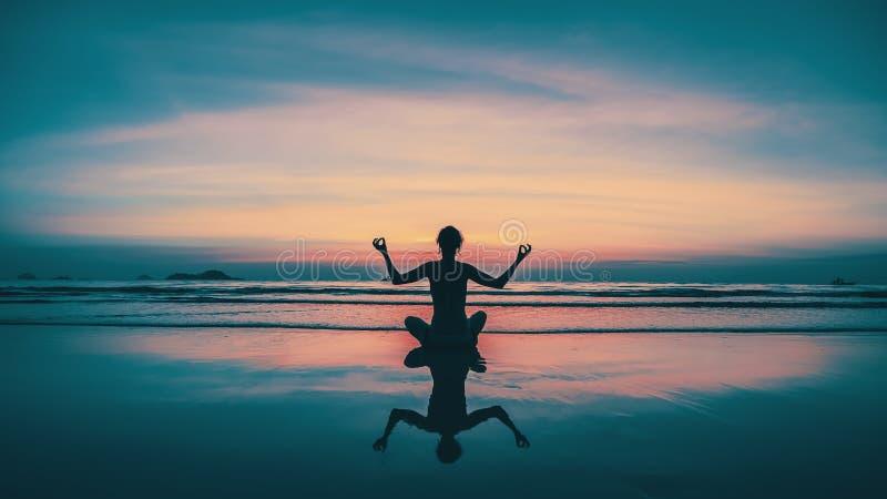 Sonnenuntergangyoga-Frauenmeditation auf Seeküste mit Reflexion im Wasser relax stockbilder