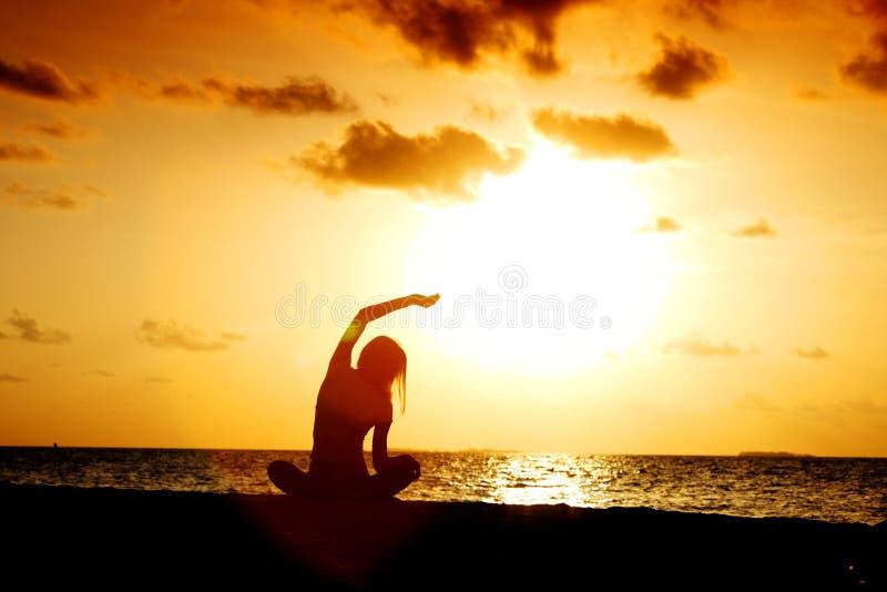 Sonnenuntergangyogafrau stockfoto