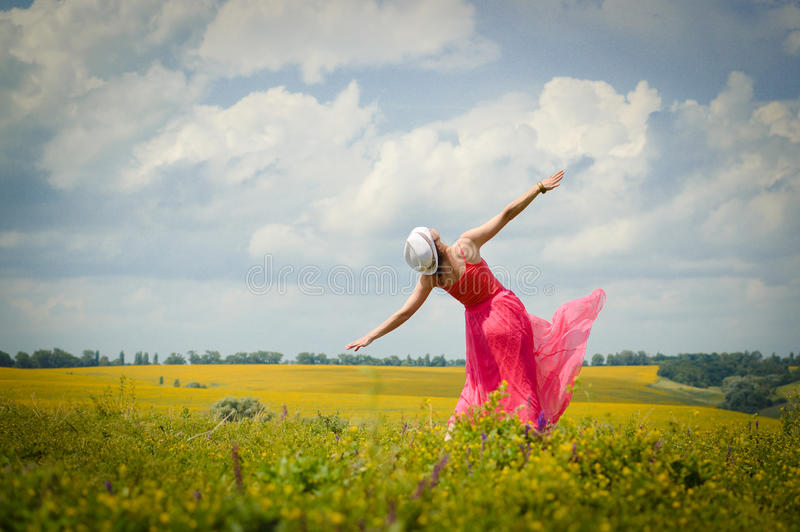 Sonnige Freiheit: Bild der schönen blonden jungen Frau im rosa Kleid, das Spaßtanzen auf grünem Kopienraum des blauen Himmels des stockfotos