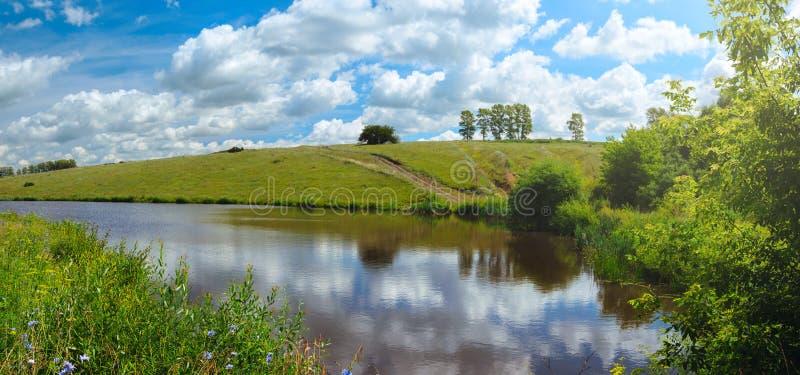 Sonnige Sommerlandschaft mit Fluss und grünen Hügeln stockfotografie