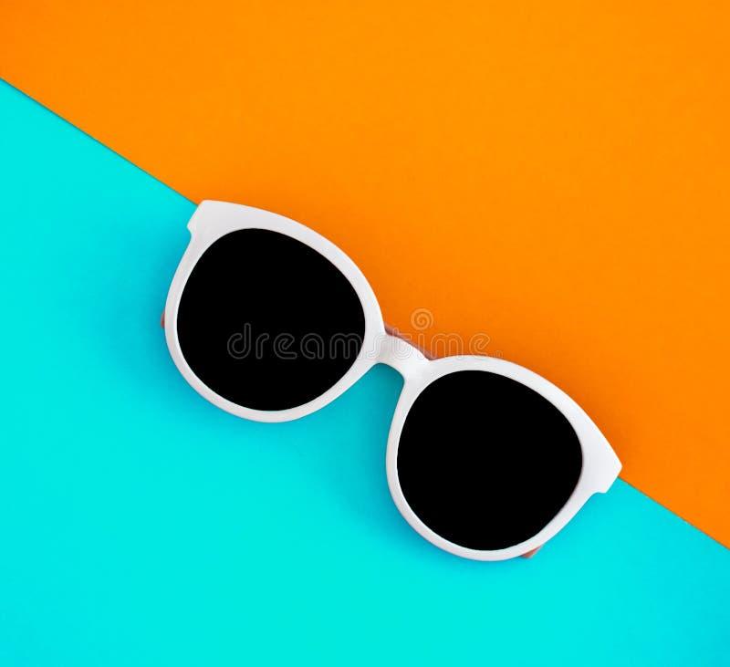 Sonnige stilvolle weiße Sonnenbrille auf einem hellen blau-cyan-blauen und gelb-orangeen Hintergrund, Draufsicht, lokalisiert Kop stockbild