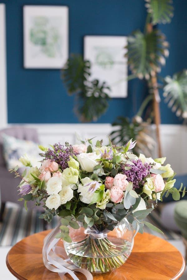 Sonniger Frühlingsmorgen im Wohnzimmer Schöner Luxusblumenstrauß von Mischblumen im Glasvase auf Holztisch Die Arbeit stockbild