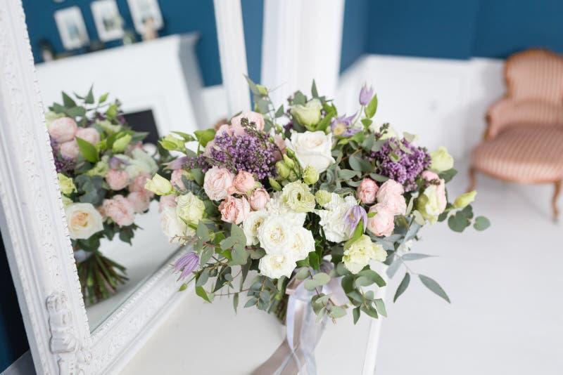 Sonniger Frühlingsmorgen im Wohnzimmer Schöner Luxusblumenstrauß von Mischblumen im Glasvase auf Holztisch Die Arbeit stockbilder
