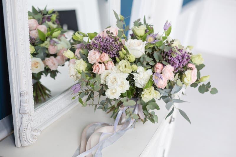 Sonniger Frühlingsmorgen im Wohnzimmer Schöner Luxusblumenstrauß von Mischblumen im Glasvase auf Holztisch Die Arbeit lizenzfreie stockbilder