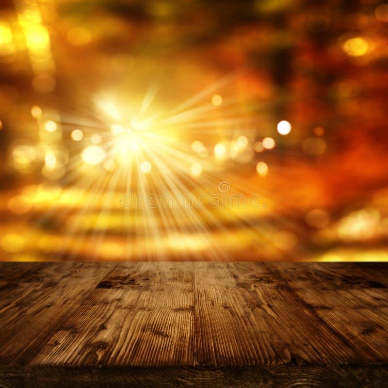 Sonniger Herbsthintergrund und -Holztisch stockfotografie