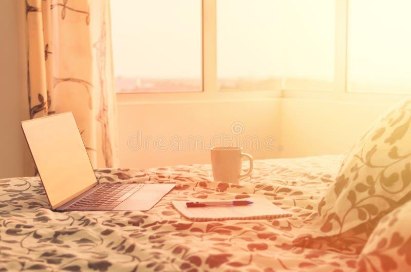 Sonniger Morgen in der modernen Wohnung - offener Laptop auf Bett gegenüber von Fenster, nahe bei Tasse Kaffee und Notizbuch stockfoto