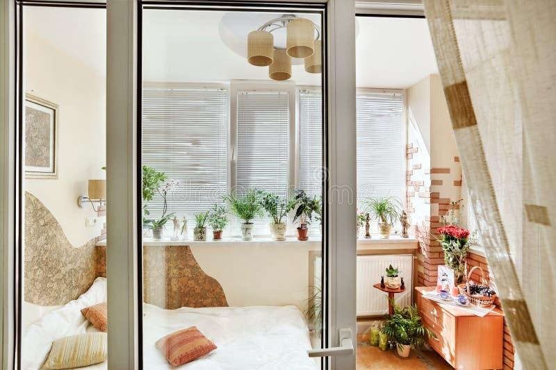 Sonniger Schlafzimmerinnenraum durch die Balkontür lizenzfreies stockbild