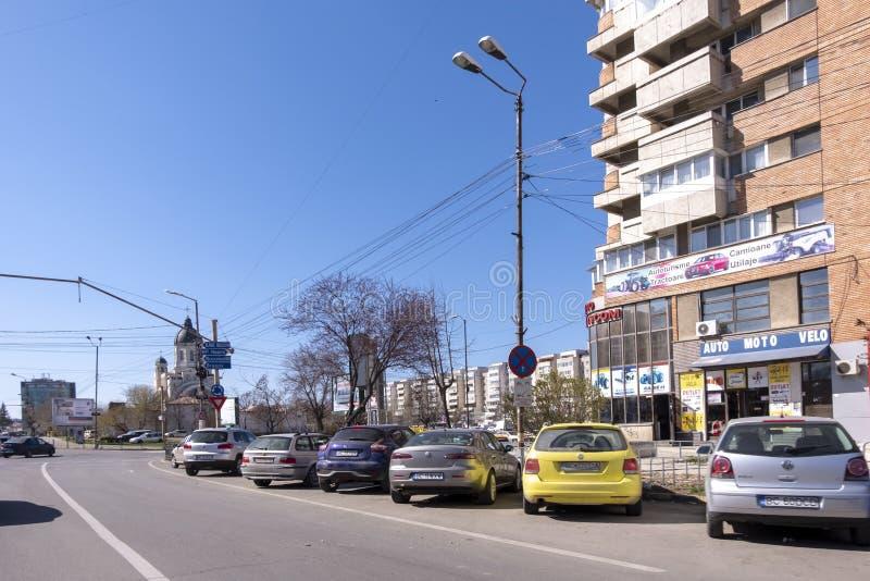 Sonniger Tag in Bacau, in einer Stadt in Nordost-Rumänien, mit Parkplatz und der orthodoxen Kirche sichtbar im Hintergrund stockfotografie