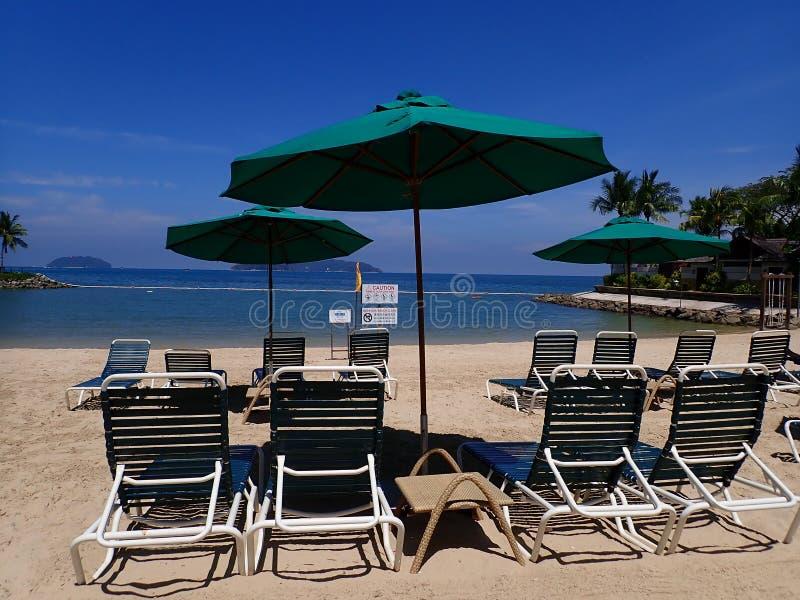 Sonniger Tag und Entspannung auf dem Strand, der auf Klappstuhl sitzt stockfotografie