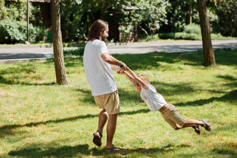 Sonniger Tagesjunger dunkelhaariger Vater und sein kleiner Sohn in den weißen T-Shirts, die den Spaß und Spielen im Freien haben lizenzfreies stockbild