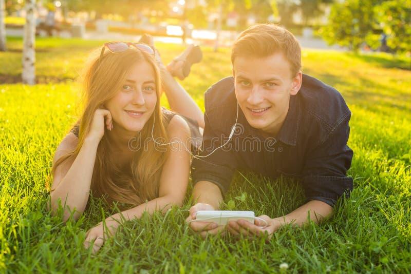 Sonniges Porträt der Lügenentspannung der süßen jungen Paare auf dem Gras hört zusammen Musik in den Kopfhörern auf Smartphone stockbilder