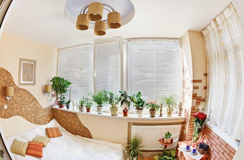 Sonniges Schlafzimmer auf Balkon mit Fenster und Anlagen stockfoto